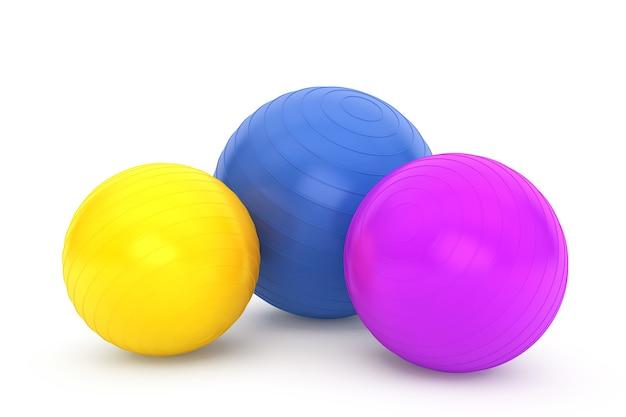 Drei bunte fitnessbälle auf weißem hintergrund