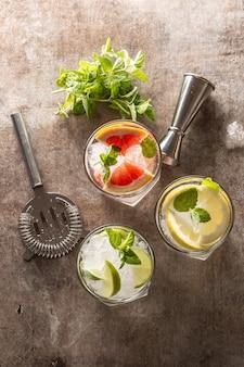 Drei bunte gin-tonic-cocktails in whiskygläsern auf der bartheke im welpen oder restaurant - ansicht von oben.