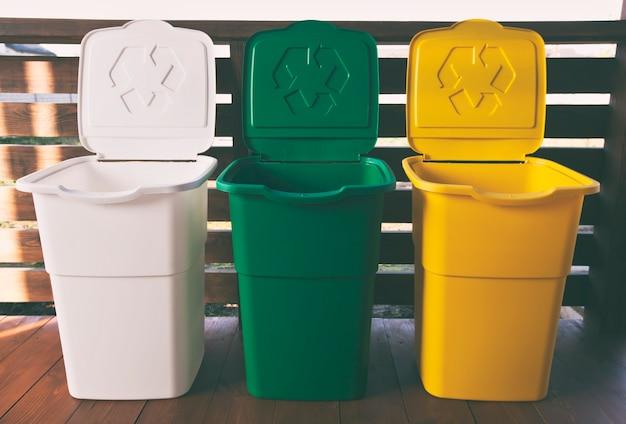 Drei bunte mülleimer zum sortieren von müll. für kunststoff, glas und papier