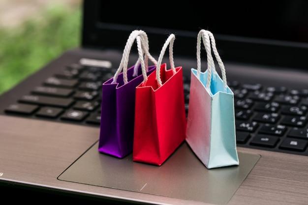 Drei bunte papiertüten auf laptop-tastatur. ideen zum online-shopping. e-commerce oder e-commerce ist eine transaktion zum kauf oder verkauf von waren oder dienstleistungen online über das internet.