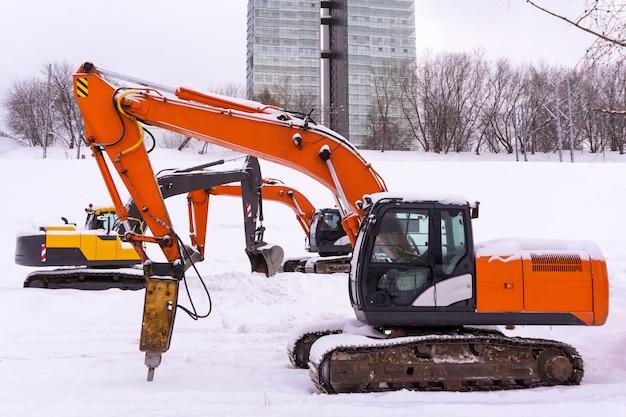 Drei bunte raupenbagger parken auf einem verschneiten feld ausleger und stöcke bilden eine enfilade