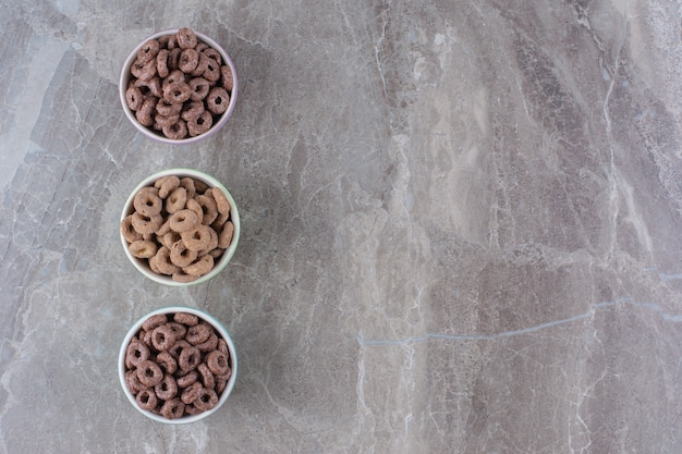 Drei bunte schüsseln mit schokoladen-müsli-ringen zum frühstück.