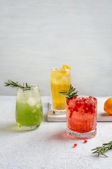 Drei bunte sommercocktails in gläsern auf weißem tisch. auswahl an frischen sommergetränken.
