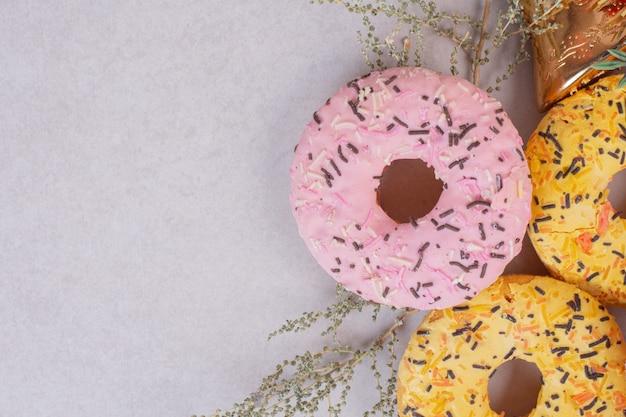 Drei bunte süße donuts auf weißer oberfläche