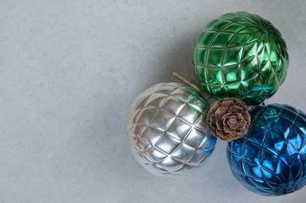 Drei bunte weihnachtskugeln mit einem tannenzapfen auf weißem hintergrund. hochwertiges foto