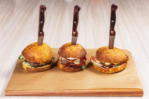 Drei burger mit messern auf hellem holztisch in einem restaurant. fast food