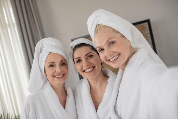 Drei charmante frauen mit schönem lächeln in bademänteln