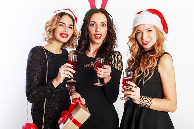 Drei charmante mädchen verbringen zeit auf neujahrsparty. ein glas champagner halten. maskeradenhüte tragen.