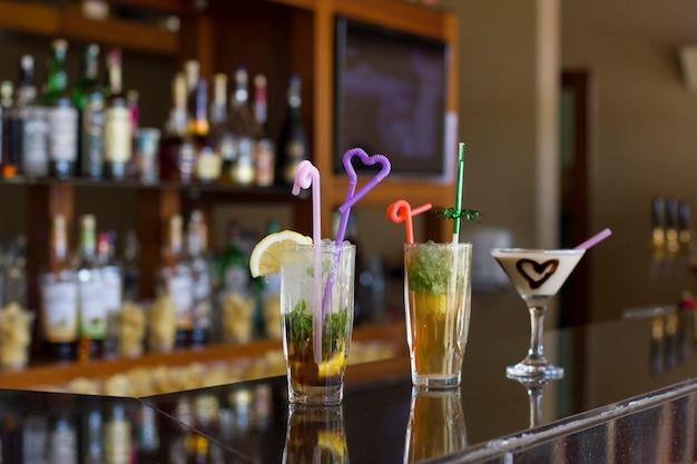 Drei cocktails an der bar - mojito mit eis und strohhalm, pina colada mit schokoladenherz
