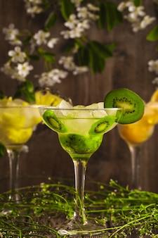 Drei cocktails mit ananas, orange und kiwi