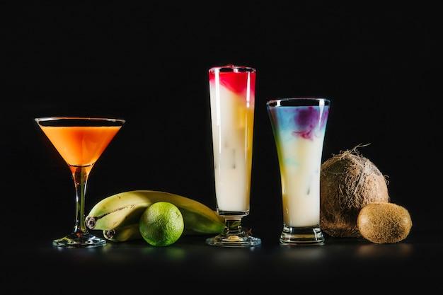 Drei cocktails und exotische früchte auf schwarzem hintergrund