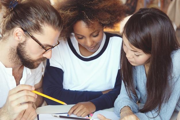 Drei college-studenten arbeiten an hausaufgaben, sitzen in der cafeteria, recherchieren, suchen im internet nach den erforderlichen informationen und verwenden ein digitales tablet.