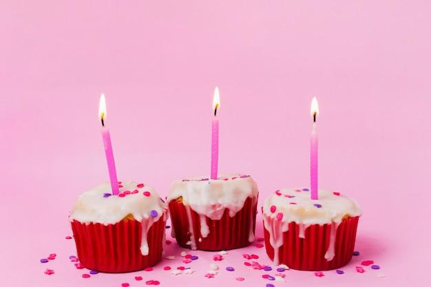 Drei cupcakes mit brennenden kerzen