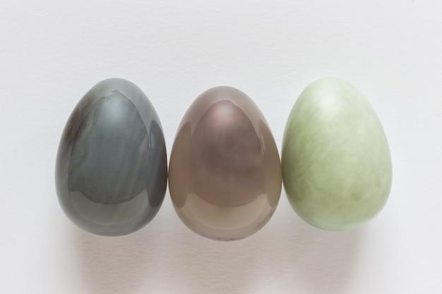 Drei dekorative edelstein-ostereier auf weißer oberfläche.