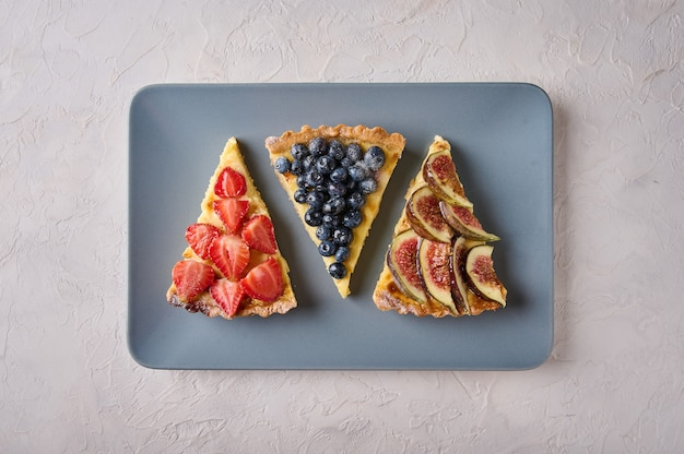 Drei desserts von tortenkuchen mit erdbeeren, blaubeeren und feigen auf rechteckigem teller auf licht