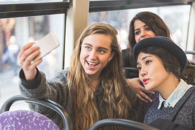Drei, die im bus ein selfie machen