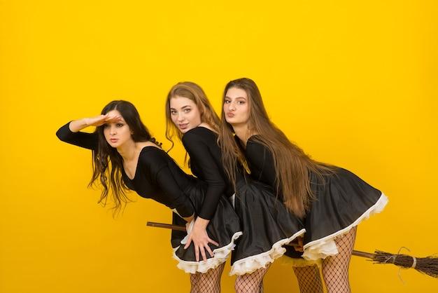 Drei dienstmädchen auf einem besenstiel im studio, hexen, böse geister.