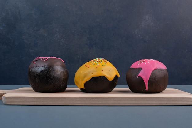 Drei donuts auf holzbrett.