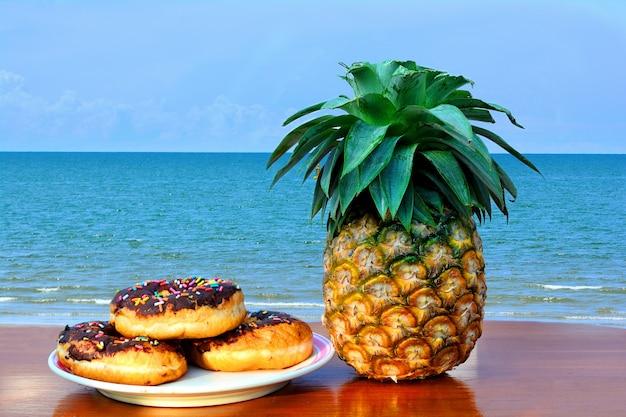 Drei donuts gelegt auf einen teller und eine ananas gesetzt auf ein hölzernes