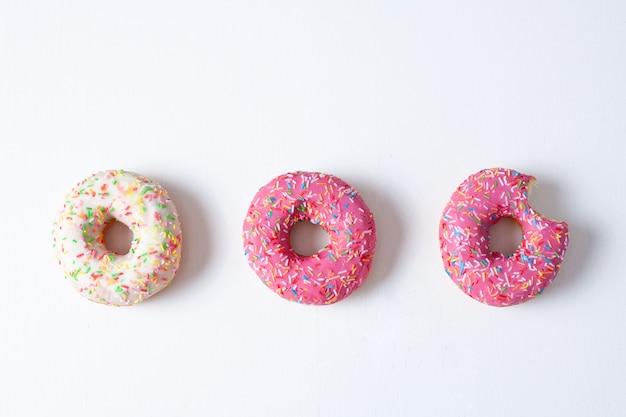Drei donuts zwei rosa und weiß gebissen auf weißem hintergrund gesamtplan hohe qualität