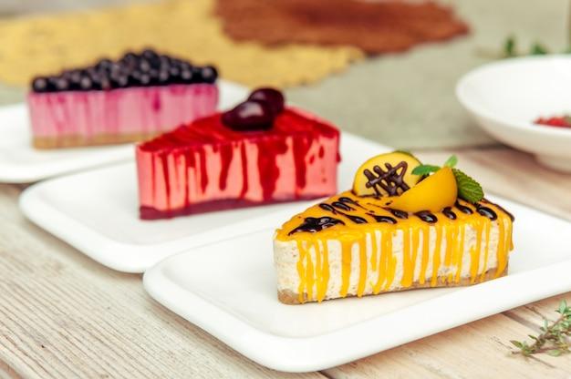 Drei dreieckige kuchenstücke mit aprikosenpflaume und johannisbeere auf rustikalem holztisch