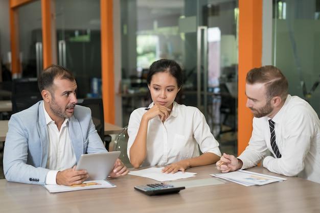 Drei durchdachte marketinganalytiker, die mit diagrammen arbeiten
