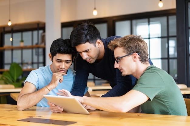 Drei durchdachte studenten, die tablet-computer verwenden
