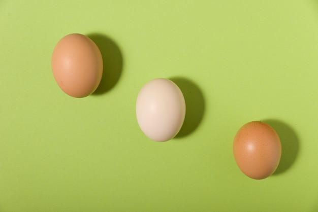 Drei eier auf grünem hintergrund und mit schatten