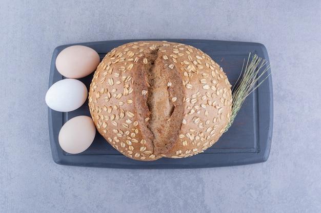 Drei eier, ein laib brot und ein einzelner weizenstiel auf einem brett auf marmoroberfläche
