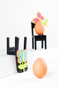 Drei eier sitzen auf schwarzen stühlen. beratung bei geschäftskonferenzen. konzept der unternehmensorganisation, brainstorming. minimale osterkonzeptidee