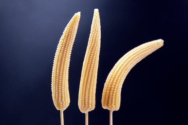Drei eingelegte mais auf einer gabel nahaufnahme auf einem dunkelblauen. essen und gemüse