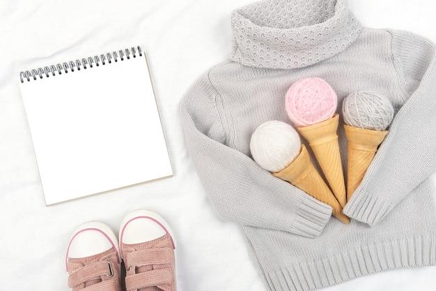 Drei eiscreme aus garn in waffeltüten auf grauem strickpullover, rosa turnschuhen und offenem notizblock