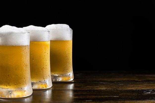 Drei eiskalte bierkrüge auf holzsockel