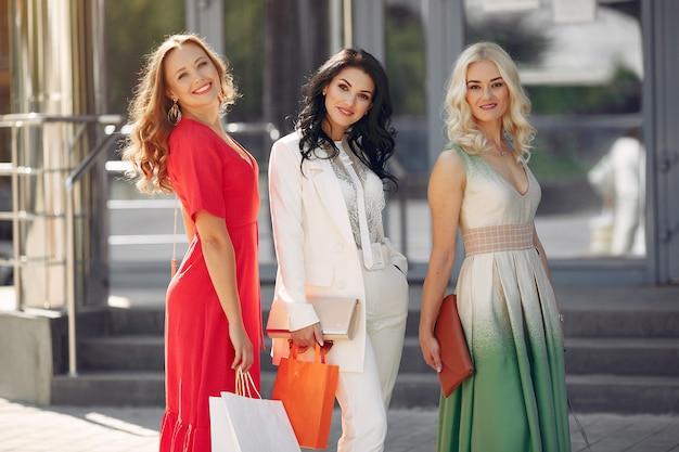 Drei elegante frauen mit einkaufstüten in einer stadt