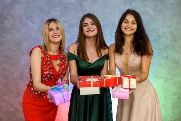 Drei elegante frauen mit geschenkboxen. frohes neues jahr feiern