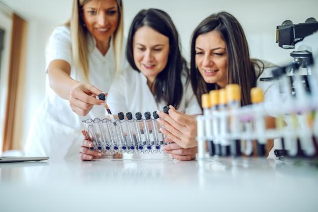 Drei engagierte schöne lächelnde kaukasische weibliche laborassistenten