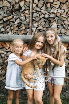 Drei entzückende glückliche kleine mädchen und eine rote katze im freien