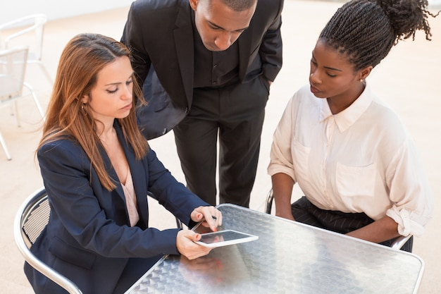 Drei ernste junge wirtschaftler, die daten bezüglich der pc-tablette aufpassen