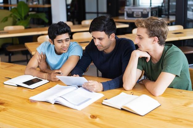 Drei ernste studenten, die tablet-computer studieren und verwenden