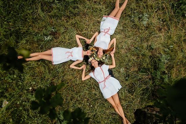 Drei erstaunliche slawische erscheinung ethnischer volksartmädchen mit kranz von blumen, die auf gras unter baum an der natur im sommer liegen. glückliche freundinnen freizeit entspannen. porträt von oben