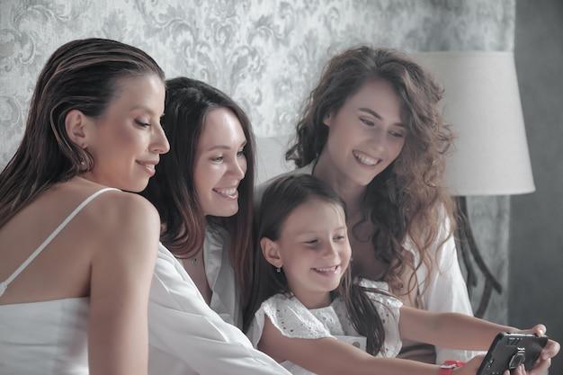 Drei erwachsene frauen und ein kleines mädchen in stilvollen, lässigen weißen kleidern verbringen zeit im bett, unterhalten sich süß, erzählen geschichten und lachen. freunde treffen sich und verbringen ihre freizeit im hotelzimmer. konzept der freundschaft