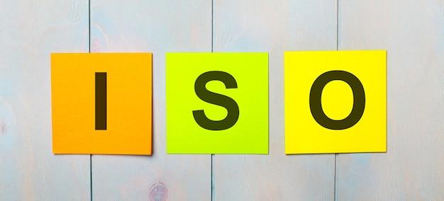 Drei farbige aufkleber mit dem text iso auf hellblauem holzuntergrund