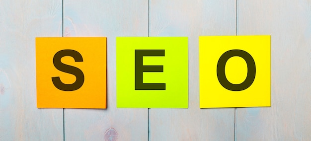 Drei farbige aufkleber mit dem text seo search engine optimization auf einer hellblauen holzoberfläche