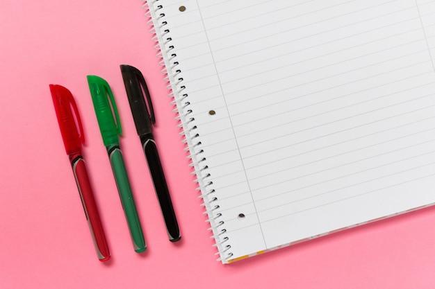 Drei farbige stifte und gezeichnetes gewundenes notizbuch auf rosa