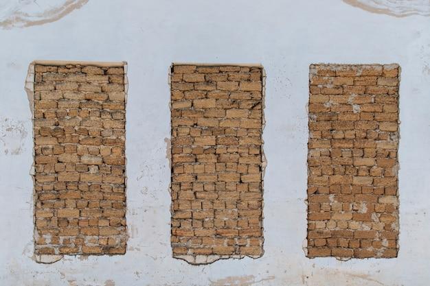 Drei fenster des alten verlassenen gebäudes sind mit ziegeln und betonblöcken bedeckt