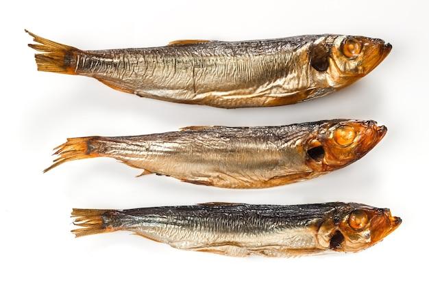 Drei fische rauchten die goldene farbe der sprotte auf einem weißen hintergrund