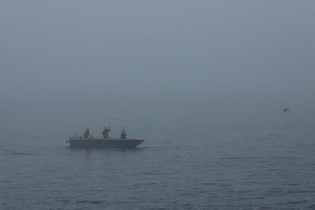 Drei fischer, die im morgendlichen seenebel von einem motorboot aus fischen.