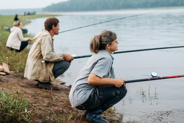 Drei fischer sitzen am ufer und fischen. fischerin.
