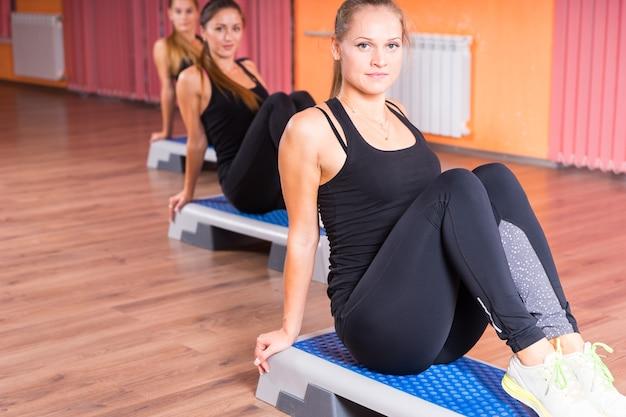 Drei fitte junge frauen sitzen auf aeroben step-plattformen im fitnessstudio und schauen in die kamera.