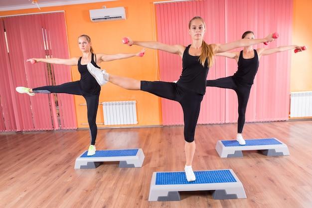 Drei fitte junge frauen strecken ihre arme und beine gleichzeitig auf fitnessplattformen im fitnessstudio.